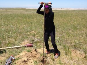 NSU marine biology major Victoria Pecci uses a bucket auger to get a sample of sand from an inactive sand dune in the Badlands in southwestern South Dakota.