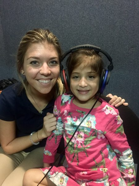 Audiology student Kasia Baginski with one of the children who received a hearing assessment in Nicaragua.