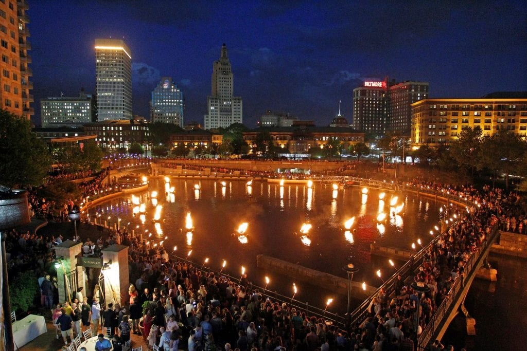 A view of the Providence River during the Waterfire celebration with basins lit up all over the river and people surrounding it.