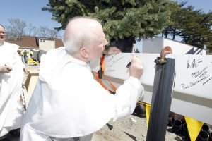 Fr. Brian Shanley signs a beam at the Ryan Center Topping Off Ceremony.