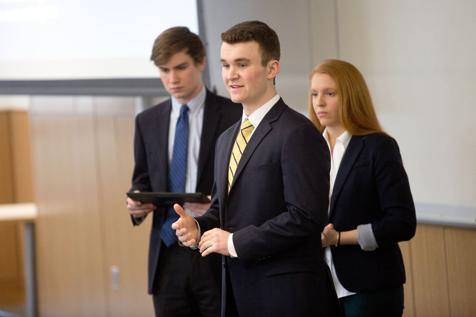 A group of three students presenting in the front of a classroom.
