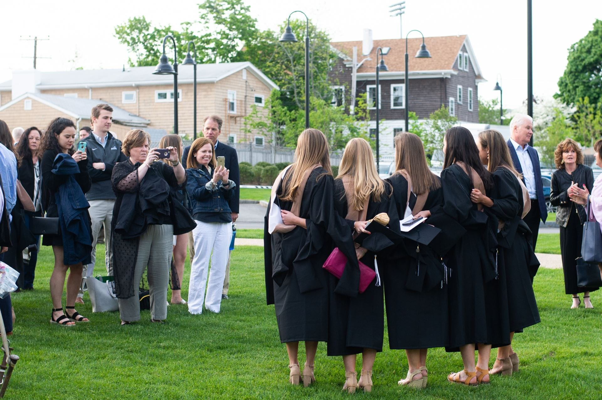 MBA graduates posing for a picture on the Ryan Center Lawn in their graduation robes and MBA hoods.