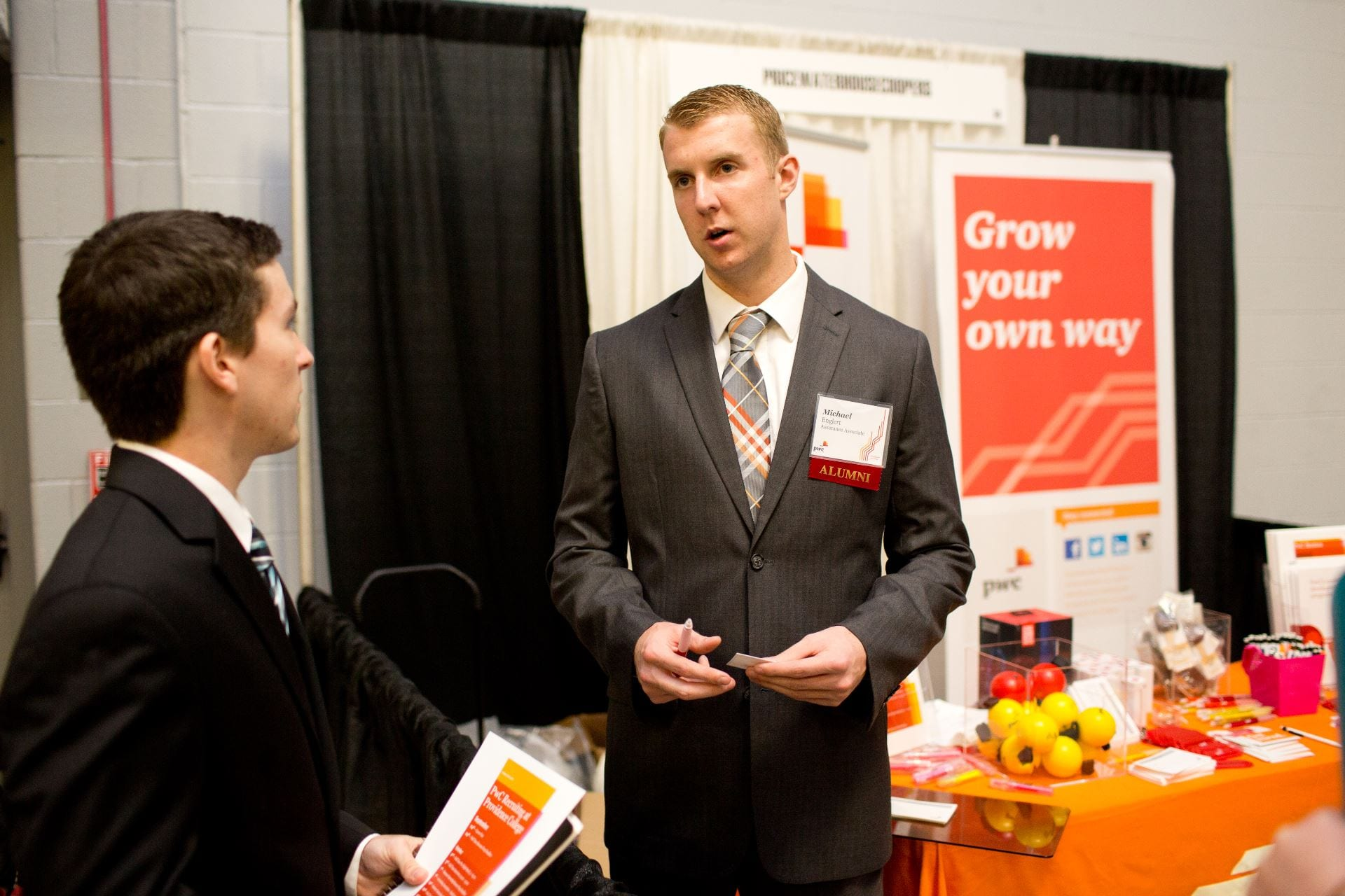 A student interacts with a current PwC employee and PC graduate about potential career opportunities.