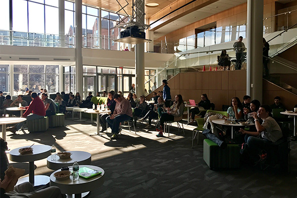 PCSB students, faculty, and administrators gather in the Palmisano Atrium for the PC Men's Basketball game watch.