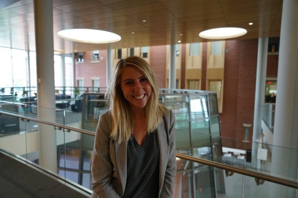 Tess Povar smiling at the camera on the 2nd floor of the Ryan Center for Business Studies with a glass walkway behind her.