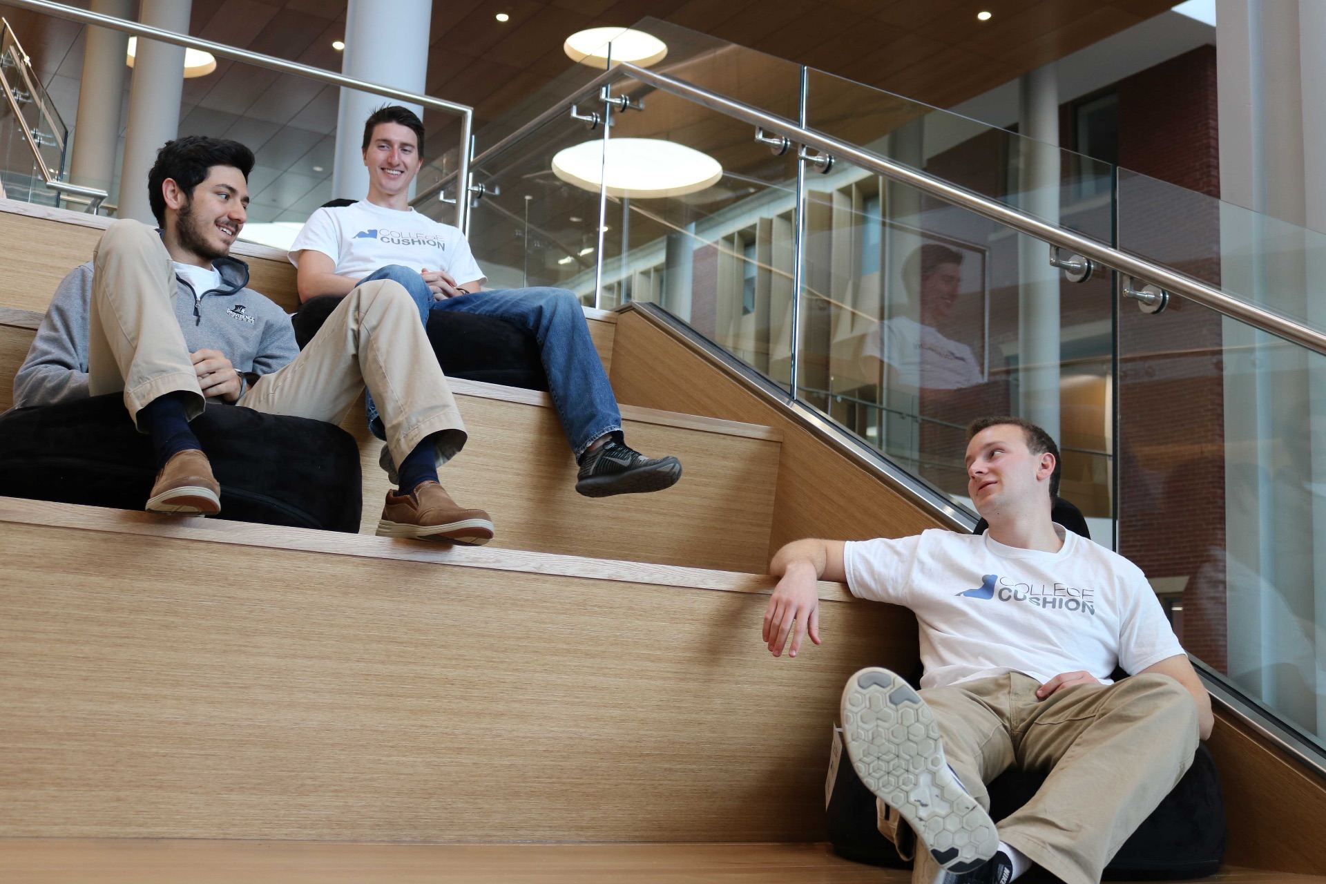 Michael Cruz '19, Shane Curran '19 and Andrew Drogan '19 sitting on the steps in the Ryan Center.