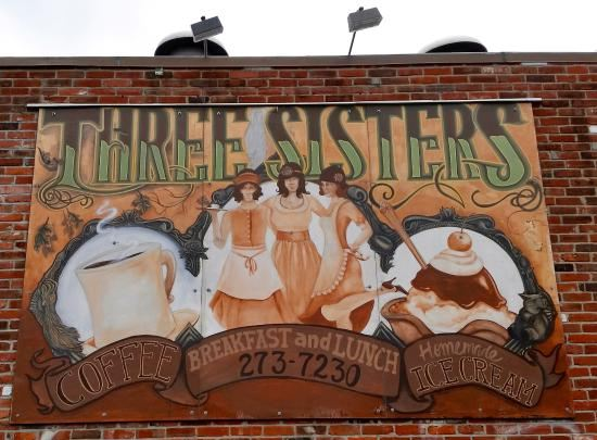 A picture of the Three Sisters sign that hangs above the cafe.