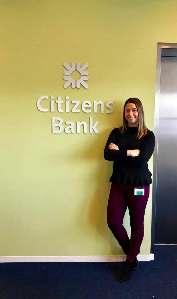 Aliza in front of a Citizens Bank sign.