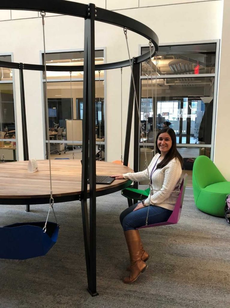 Lauren sitting in a hanging chair in her athenahealth office.