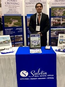"male in a black suit standing at a booth with a blue sign reading ""Saletin Real Estate Group"""