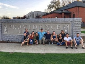 group of people dressed in summertime clothing huddled around Providence College sign in Huxley Circle