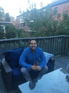 man sitting on a blue chair holding a glass of white wine; outside on a rooftop