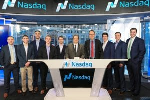 group of 10 men at NASDAQ, wearing suits and standing behind a desk
