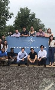 a group of 14 interns gathered around a blue Lockheed Martin sign