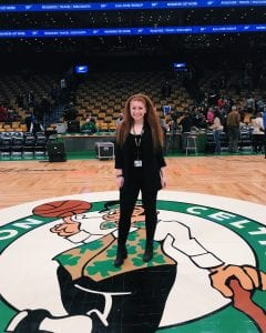 girl in black clothing with long red hair standing center court where the Boston Celtics play