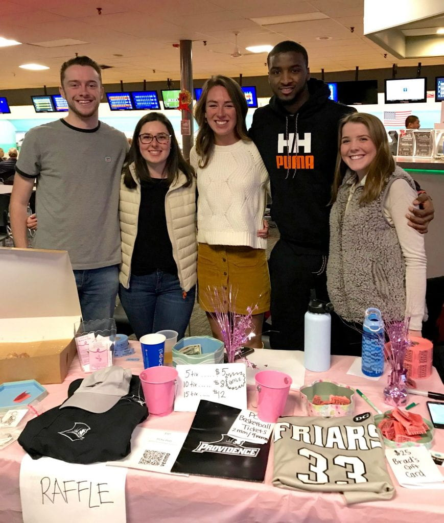 Five students stand behind a raffle table at a bowling fundraiser.