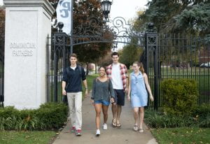 four students walking under an iron wrought gate