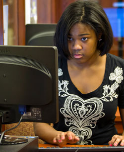 A student uses a computer intently, in the writing center