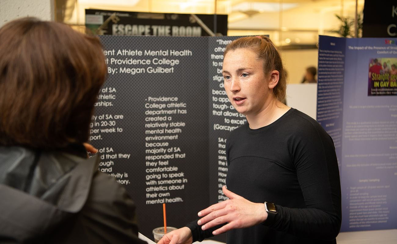 A PC student presents a poster on Student-Athlete mental health