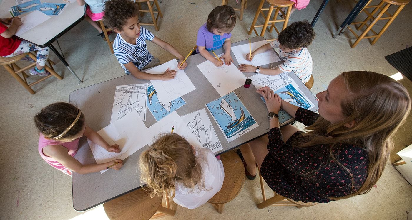 Some very cute kids working with an instructor on a coloring page of a sailboat