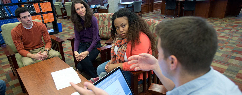 Dr. Jennifer Van Reet meeting with 3 students in the library