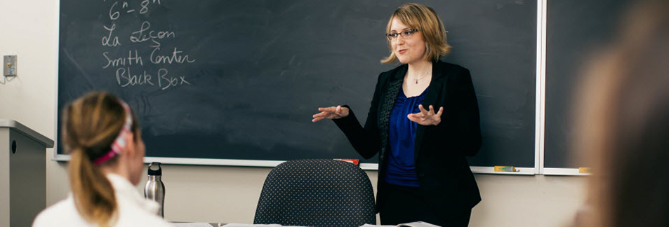 Teacher talking to class in front of chalkboard