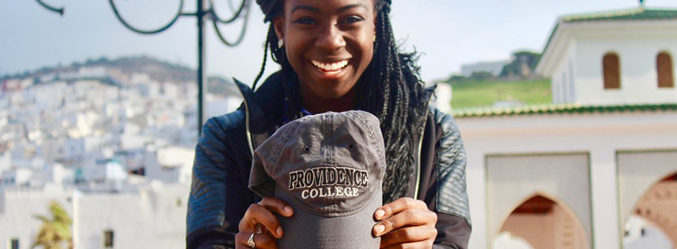 Student holding a providence college hat