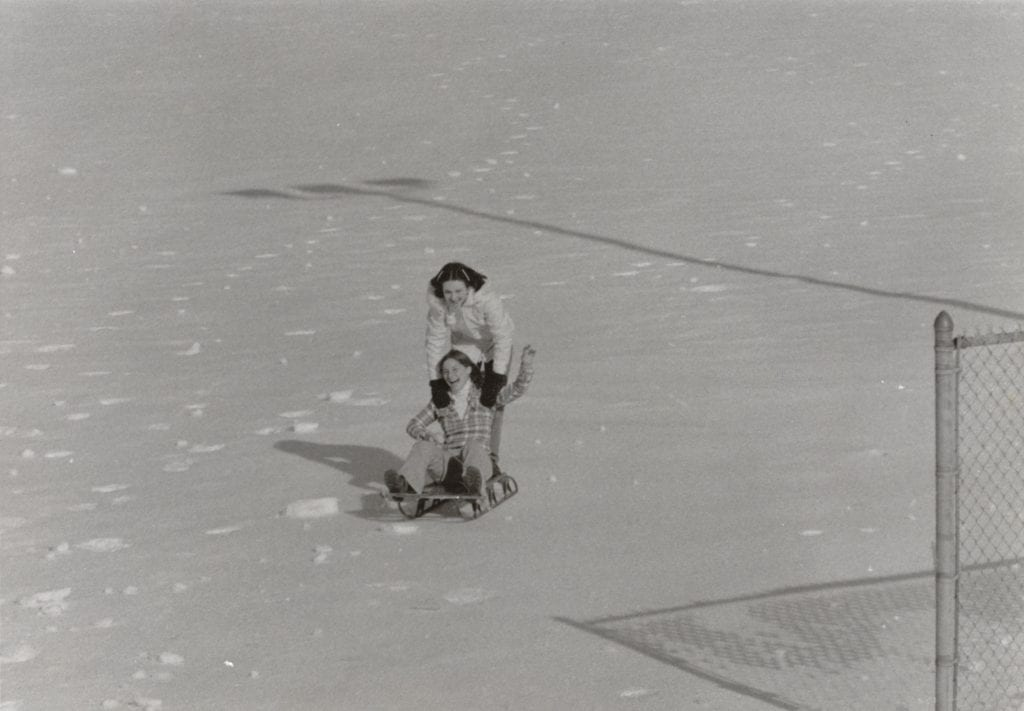 Image of two young women sledding during the blizzard of 1978