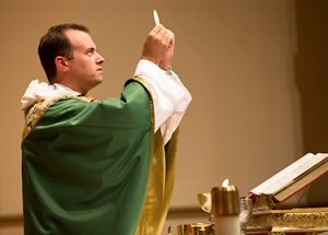 Father Cuddy holding the eucharist