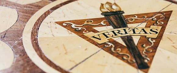 Image of the Veritas logo- a torch in front of a triangle with the word Veritas overlaid in front