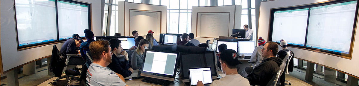 Students surrounded by LED screens in a business school classroom