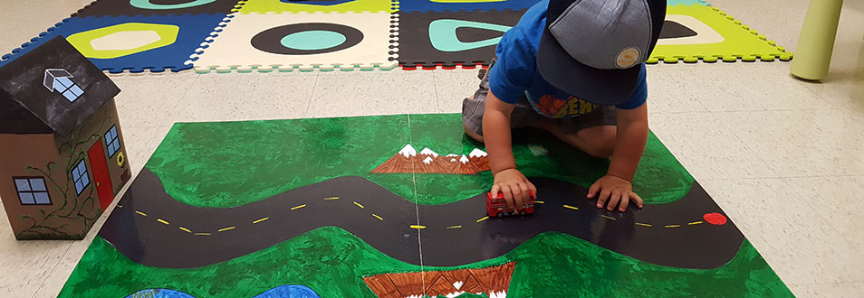 A child playing with a toy truck over a play mat decorated like a road and a green field