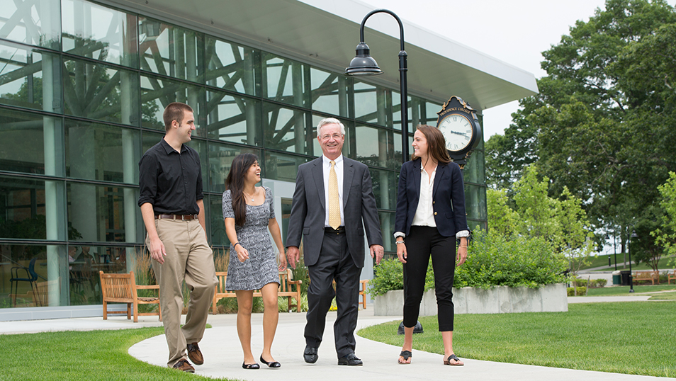 Students and businessman walking on campus