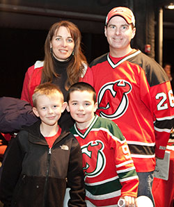 A member of the Alumni club and their family wearing New Jersey Devil uniforms