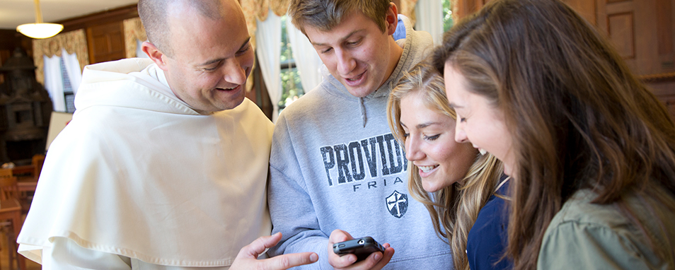 Fr. Cuddy with students looking at a phone