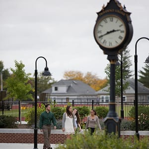 Students walking on campus next to our campus clock