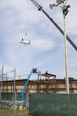 Schneider Arena beam being hoisted up