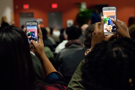 Students taking photos with their cellphones at an event