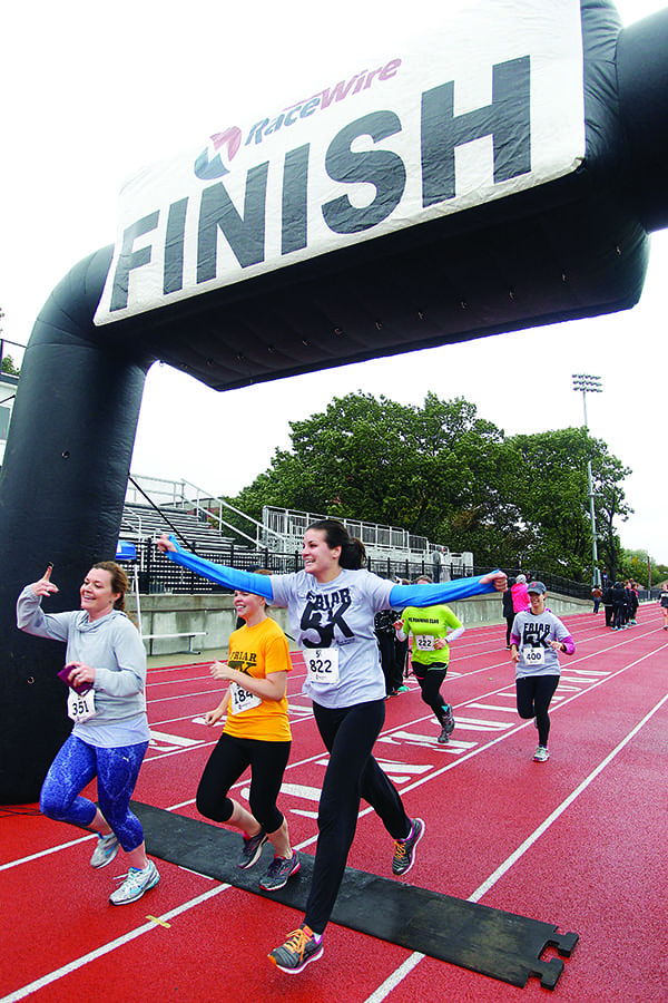Also during St. Dominic Weekend, exultant runners cross the finish line at the annual Friar 5K. (Stew Milne Photo)