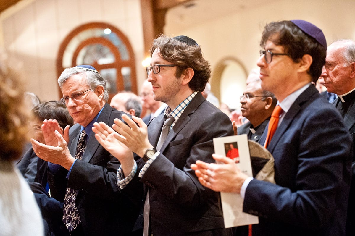 Dr. James S. Waters, center, assistant professor of biology and a member of the Jewish-Catholic Theological Exchange Committee, applauds Cardinal Dolan.