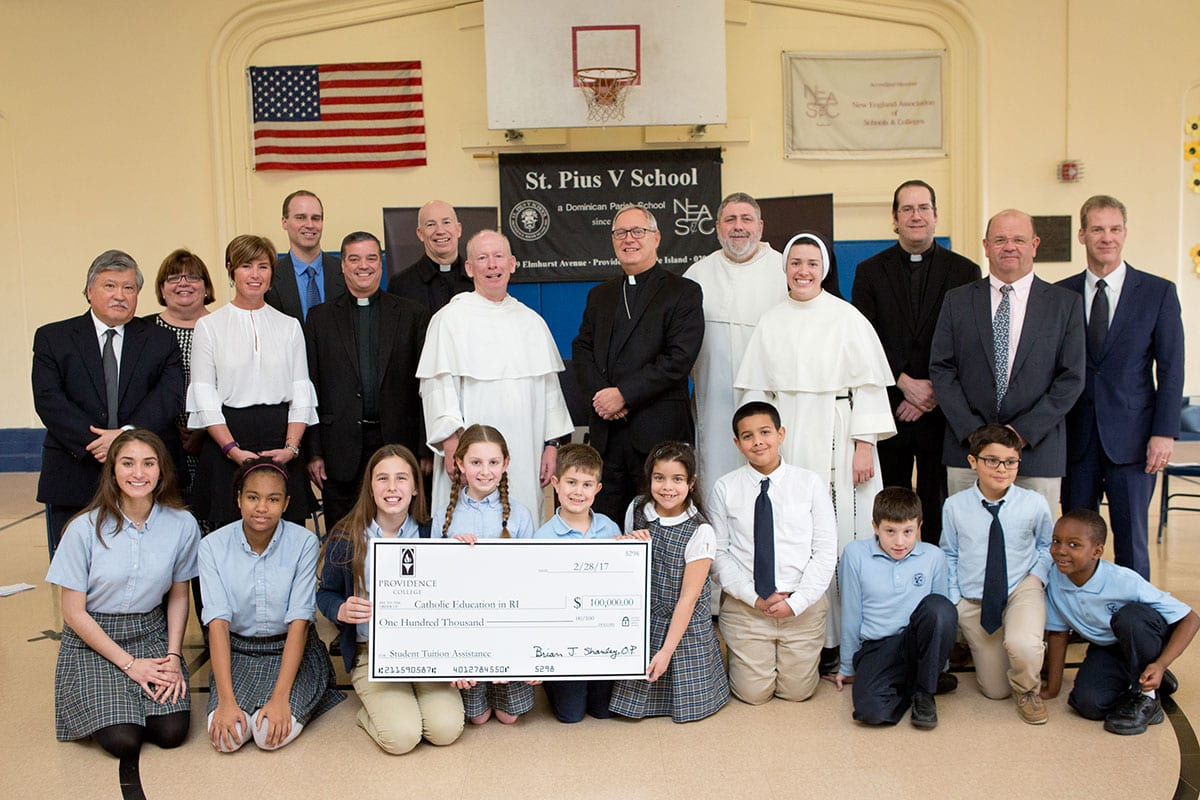 College representatives, diocesan officials, and Catholic school children at the announcement of PC's $100,000 gift.