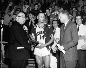 Lenny Wilkens '60 accepts the Most Valuable Player trophy after PC won its own holiday tournament during the 1959-60 season. Rev. Aloysius B. Begley, O.P. '31, athletic director, presents the award as Head Coach Joe Mullaney looks on.