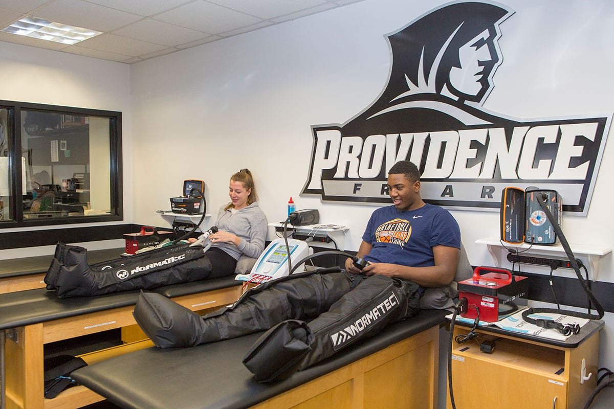 Floor Rozemeijer '20 of the field hockey team, left, and Kalif Young '20 of the men's basketball team share a laugh as they get treat-ment through the new NormaTec compression-boot systems.