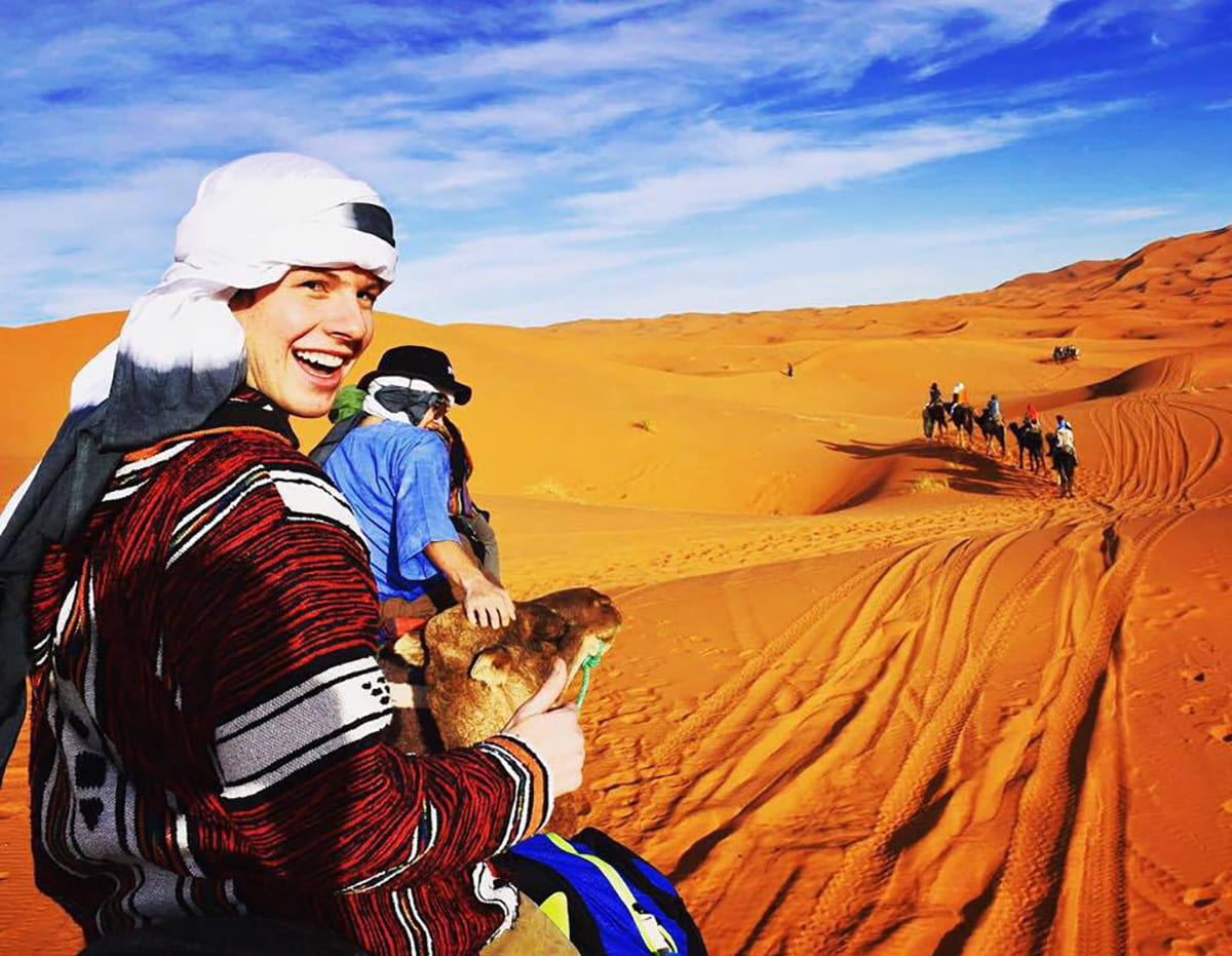From left, Connor Kinkead '17 and Conor Gibbons '17 join a group for a camel ride in a Moroccan desert.