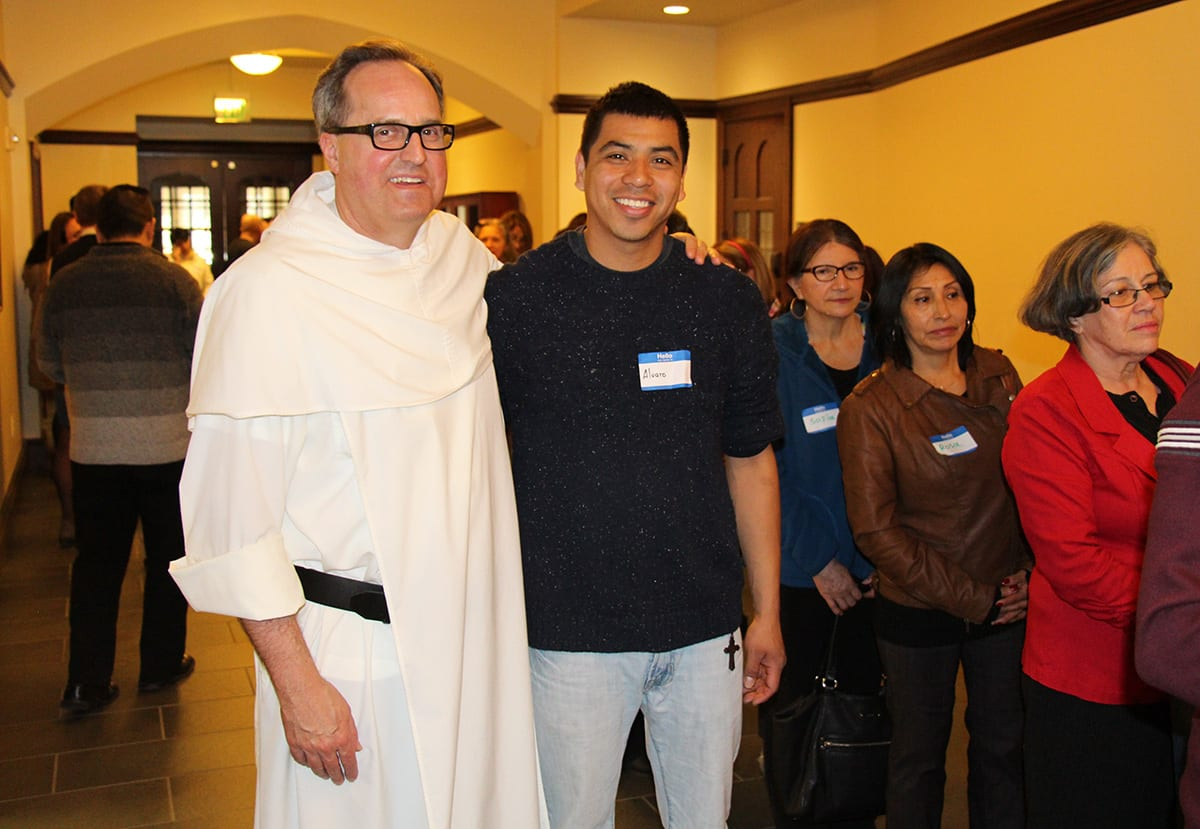 Rev. David T. Orique, O.P. greets one of the Latino Symposium guests during a break in the programming.