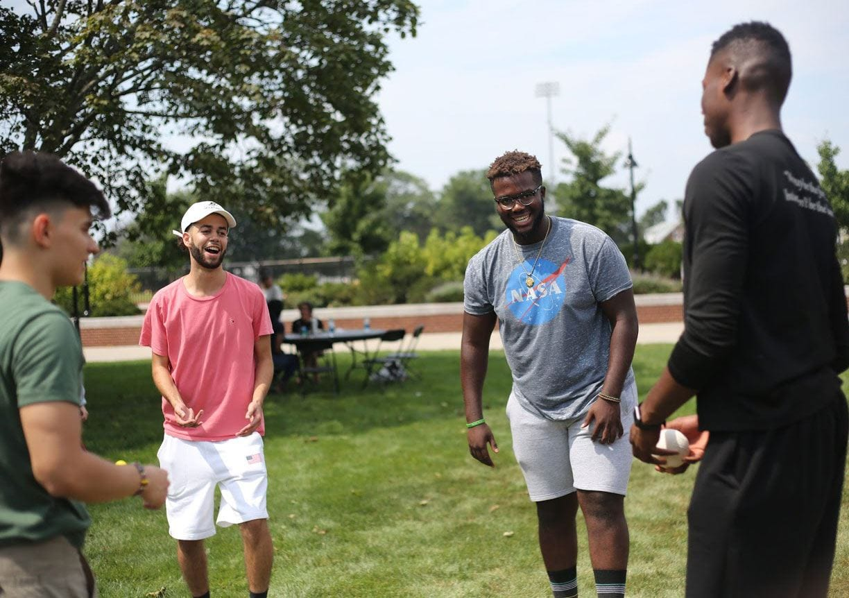 From left, Mateo Godoy '21, Jeffrey Acosta '21, Princely Tamfu '21, and Samuel Adefiyiju '21 play Spikeball during a Transitions Program reception on the Slavin Center lawn. The pre-orientation program for multicultural and first-generation college students helps participants get acclimated with all aspects of PC.​ (Photo: Bradley Camilo '20)