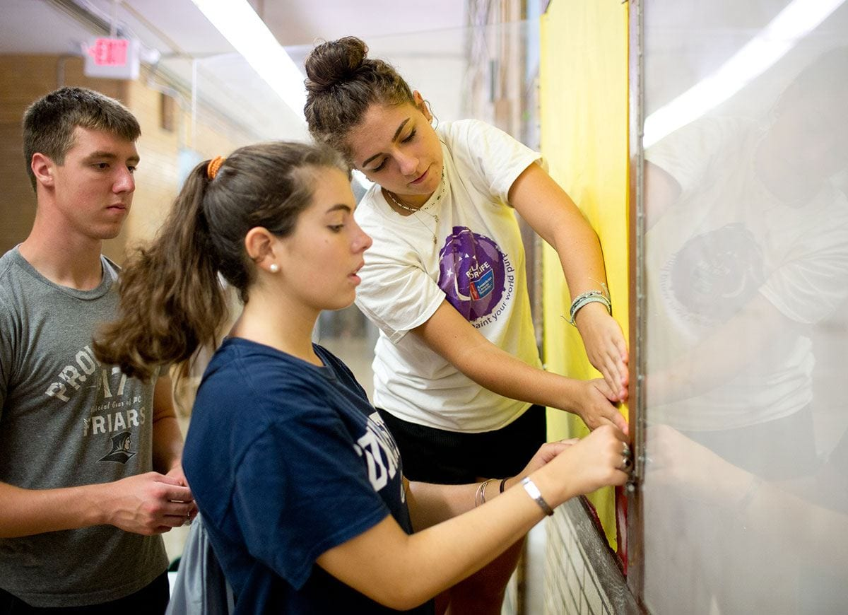 From left, Connor Christuk '21, Katie Mann '21, and Katrina Aucello '21 work on a hallway poster board at the Robert F. Kennedy Elementary School as part of Urban Action.