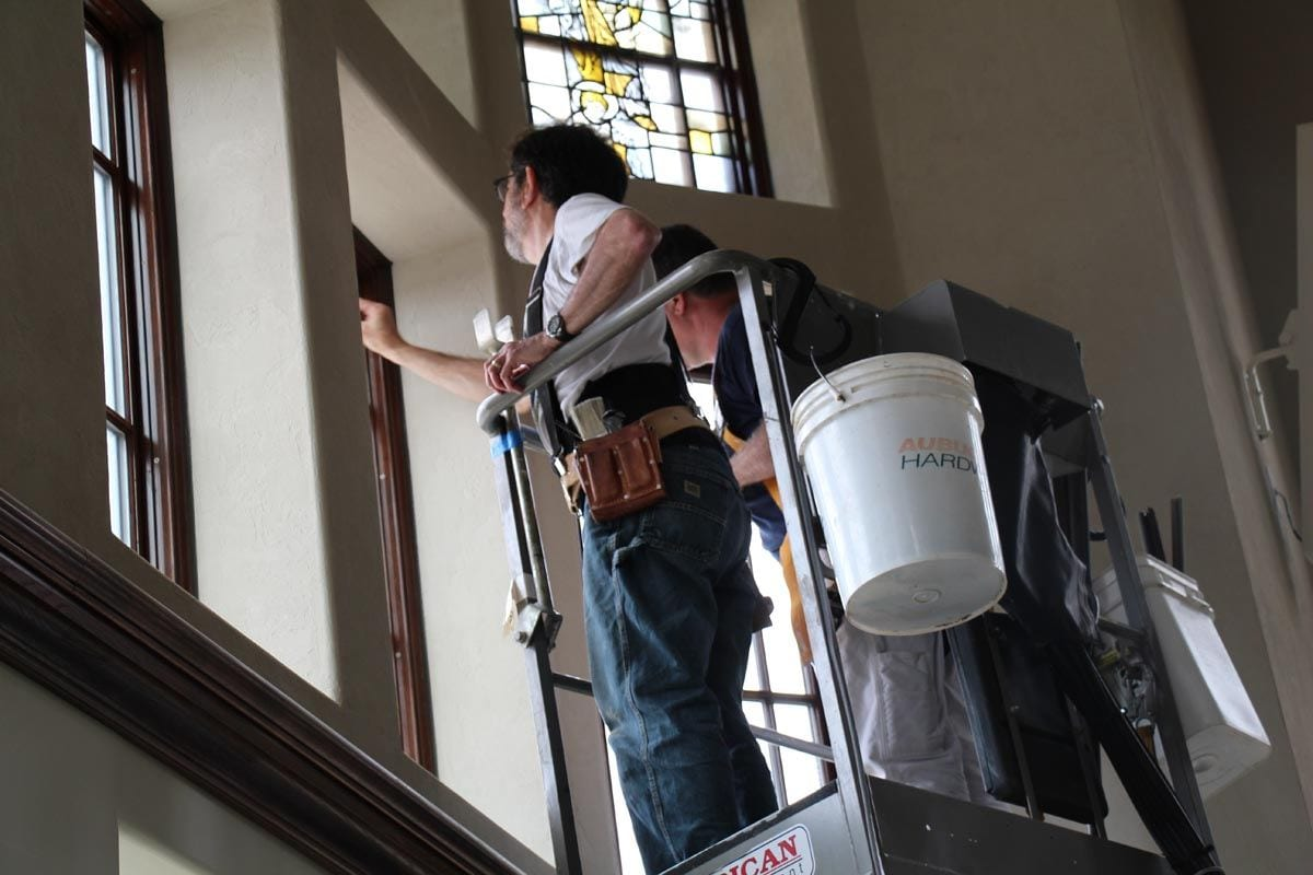 Mark Liebowitz installing a stained-glass window in the Ruane Center.