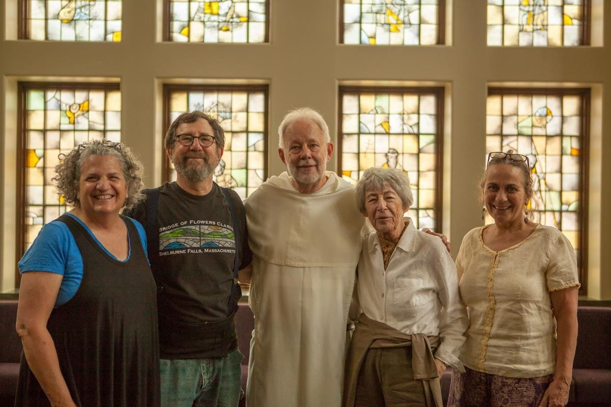 Standing before the stained-glass windows in the Ruane Center for the Humanities are, from left, Nancy Katz, Mark Liebowitz, Rev. Kevin D. Robb, O.P. '71, Sylvia Nicolas '01Hon., and her assistant, Susan Brown.