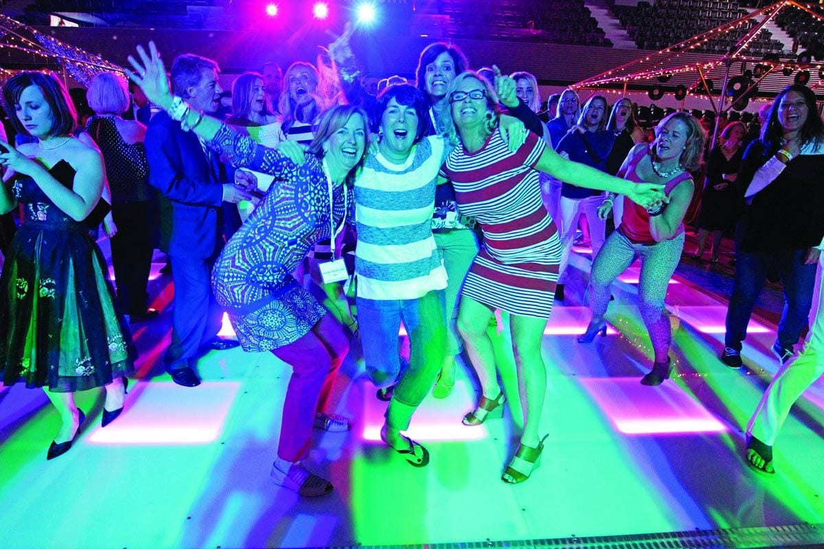 Graduates from the Class of 1987 swing to the music of Tavares at the Dancing Through the Decades event as part of the centennial celebration during Reunion Weekend 2017. From left are Deirdre Dowd '87, Marybeth Noonan '87, Karen Kenney '87, and Kathy Hussey O'Brien '87.
